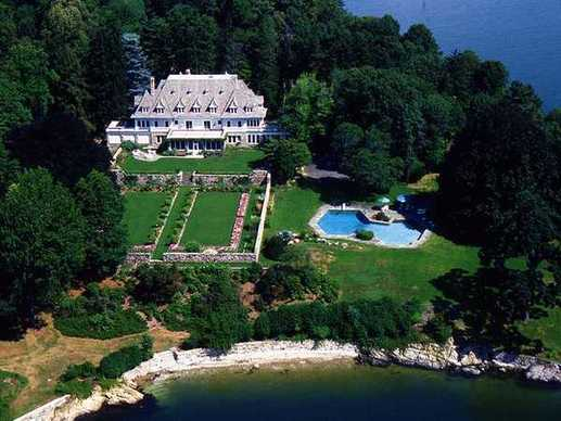 An aerial view shows the relation of the mansion to the swimming pool and shoreline.