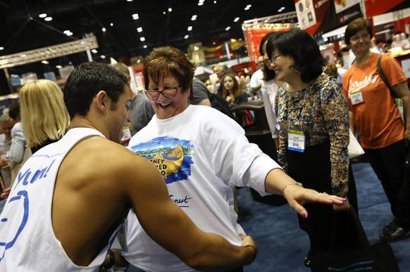 Skyler Mason whose father owns Honey Smoked Fish Co. out of Colorado puts a t-shirt for the company on Eileen Stillwell of New Lenox as a line of customers wait their turn. Thousands of people from all over the world wandered the National Restaurant Association Show at McCormick Place in Chicago.