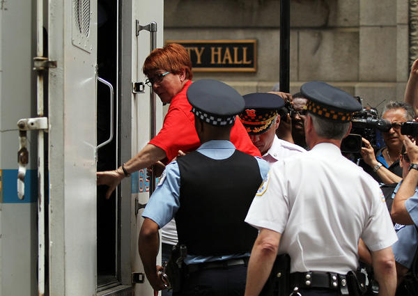 A protester is arrested at City Hall in Chicago after blocking access to elevators in the building to protest against school closings.