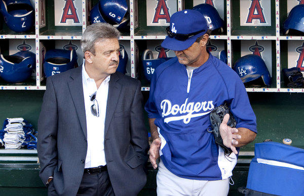 Dodgers General Manager Ned Colletti talks with Manager Don Mattingly before a game against the Angels in 2011.