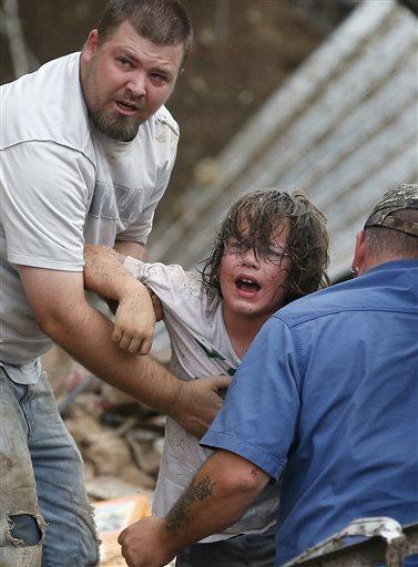 A child is pulled from the rubble of Plaza Towers Elementary School after a tornado in Moore, Okla.