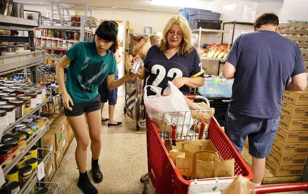 Volunteer Emily Heng, of Glen Ellyn, left, helps Doreen Danner, of Glen Ellyn, select items Monday at a food pantry run by the People's Resource Center in Wheaton.