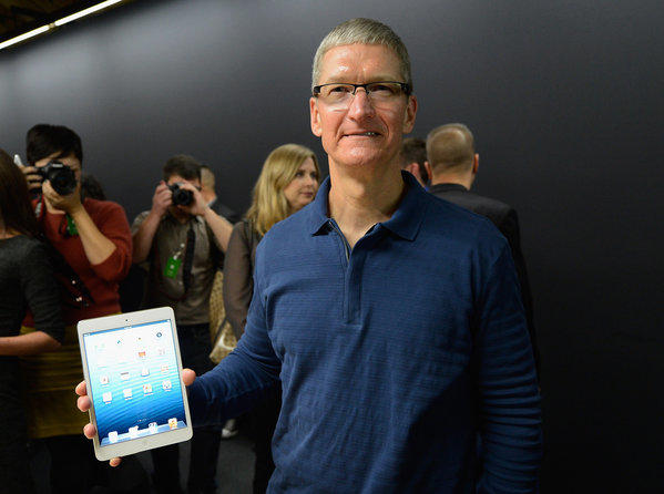 Apple CEO Tim Cook displays an iPad Mini after it was unveiled in San Jose last year. The company's tax practices are the subject of a new congressional investigation.