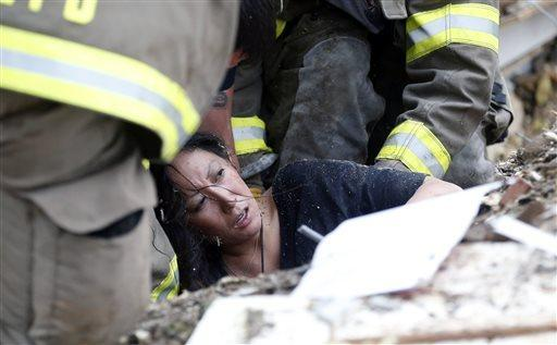 A woman is pulled from tornado debris at the Plaza Towers Elementary School in Moore, Okla.