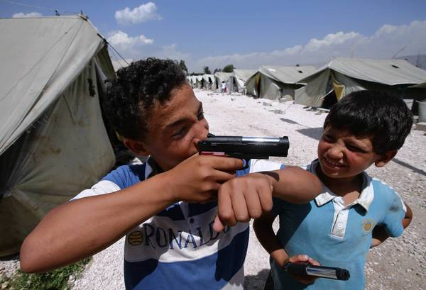 Jamal, an 11-year-old Syrian refugee, points his toy gun while playing with a friend at a refugee camp in the Lebanese town of Marj.
