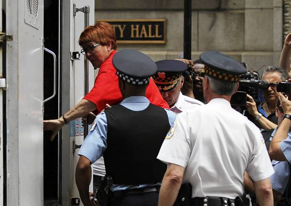 A demonstrator is arrested Monday at City Hall after blocking access to elevators in the building to protest proposed school closings. The school board is set to vote on the school closing plan Wednesday.