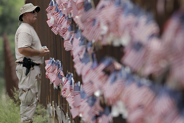 Richard Loomis Jr., of Yarmouth, Maine, looks at the flags hanging on the International border wall in Hereford, Ariz. where tea party groups converged to show support for Arizona's controversial immigration law.