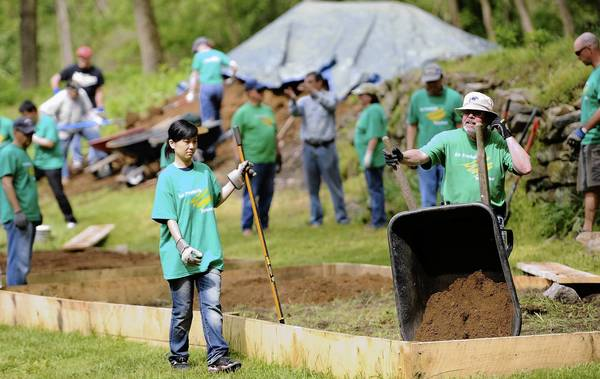 Eric Minford of Laurys Station (right) dumps a wheelbarrow of rich soil into a planting box Thursday, when a group of Air Products volunteers spruced up an area along the Lehigh Canal in Freemansburg.