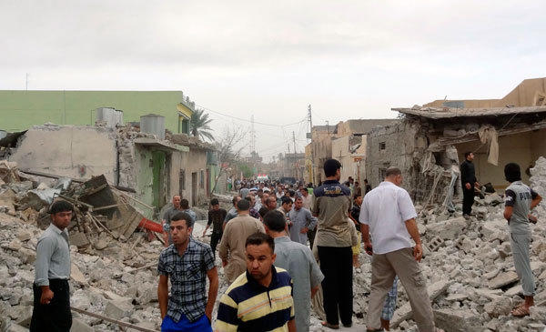 Residents stand amid rubble at blast scene in Tuz Khormatu town in northern Iraq May 21, 2013. Three persons were killed and 52 others were injured after two car bombs were set off in Tuz Khormatu on Tuesday, according to the police.