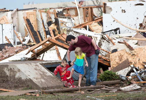 A man and two children walk through debris after a huge tornado struck Moore, Oklahoma, near Oklahoma City, May 20, 2013.