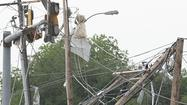 Power poles and lines lie tangled after a tornado struck Moore, Oklahoma