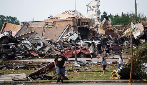 People walk near destroyed buildings and vehicles after a tornado struck Moore, Oklahoma, near Oklahoma City, May 20, 2013.