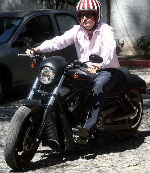 Chivas USA owner Jorge Vergara rides his motorcycle while wearing a helmet painted with Chivas' colors.