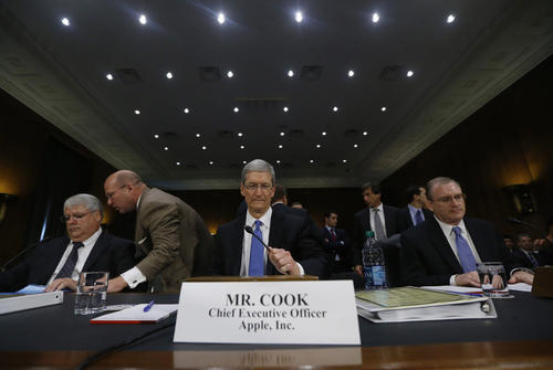 Apple CEO Tim Cook (C), CFO Peter Oppenheimer (L) and Apple Head of tax operations Philip Bullock appear before a Senate homeland security and governmental affairs investigations subcommittee hearing on offshore profit shifting and the U.S. tax code, on Capitol Hill in Washington, May 21, 2013. Apple Inc came under fire on Tuesday at a Senate hearing over an investigation that alleged the U.S. high technology icon has kept billions of dollars in profits in Irish subsidiaries and paid little or no taxes to any government.   REUTERS/Jason Reed    (UNITED STATES - Tags: POLITICS BUSINESS TPX IMAGES OF THE DAY)