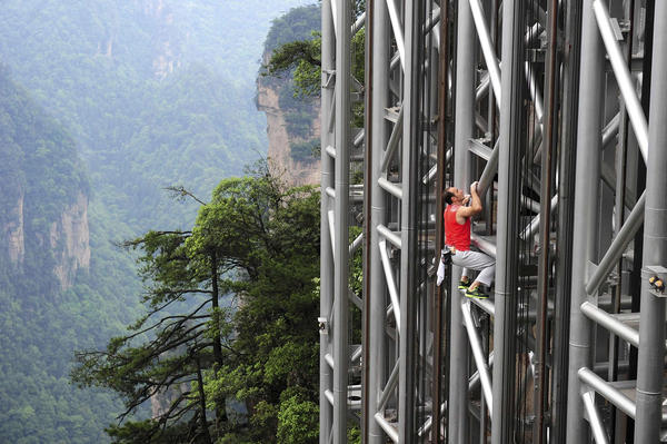 France's daredevil climber Jean-Michel Casanova climbs the Bailong Elevator near a cliff in the Wulingyuan tourism area of Zhangjiajie, Hunan province May 18, 2013. The 330-metre-high (1,083 feet) elevator, opened in 2002, was claimed to be the highest and heaviest outdoor elevator in the world by local government officials. Casanova successfully climbed the outdoor section of the elevator (172 metres, 564 feet) on Saturday without safety equipment in 68 minutes and 26 seconds, local media reported. REUTERS/China Daily (CHINA - Tags: SOCIETY SPORT TPX IMAGES OF THE DAY) CHINA OUT. NO COMMERCIAL OR EDITORIAL SALES IN CHINA