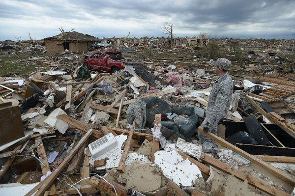 A resident of Moore, Okla., surveys damage left behind by the devastating tornado that passed through on Monday. It was the third megatornado to strike there since 1999.