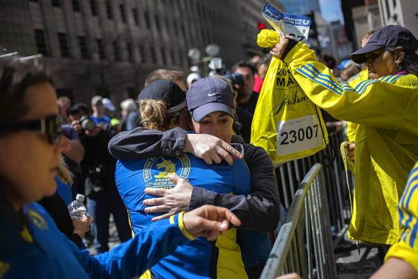 Runners embrace after picking up their medals near the finish line of the Boston Marathon on April 16, a day after tragedy struck during the day of the race in Boston.