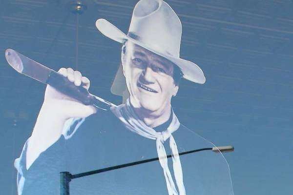 Reflection of John Wayne figure in the window of the Chamber of Commerce in Winterset, Iowa, his birthplace.