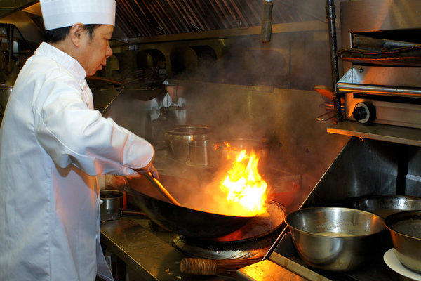 Head Chef Tony Luk works over a flaming dish in the kitchen of the Jade Seafood Restaurant in Richmond, BC.