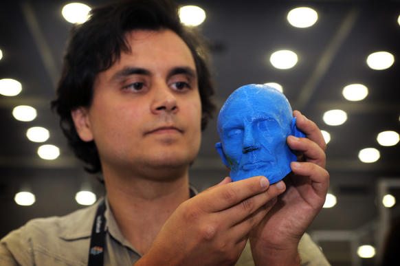 Adam Metallo with the Smithsonian Institution Digitization Program Office holds an ABS plastic 3D print from an affordable printer. The blue head is hollow, but is available with infill. The original head is a life mask of Abraham Lincoln from the National Portrait Gallery.