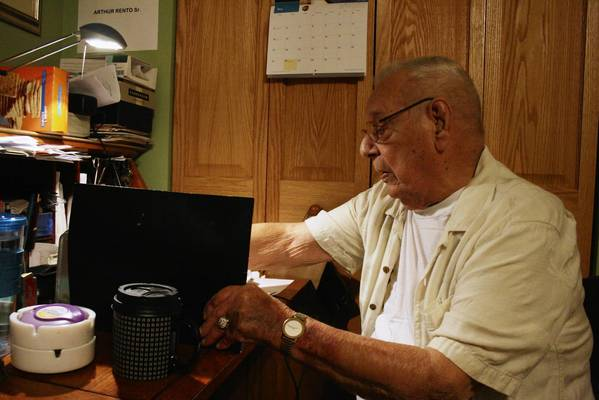 Glenview resident Arthur Rento, 90, a veteran of World War II, sifts through his war memorabilia in his room on May 17.