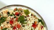 Rice salad takes a colorful turn with cooked small shrimp, fresh arugula, tomatoes, minced red onion and toasted pine nuts. The whole dish comes together in about 45 minutes. /