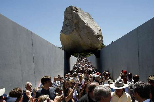 """Michael Heizer, shown in cowboy hat and yellow shirt at LACMA, and his piece """"Levitated Mass"""" are the subject of a new documentary."""