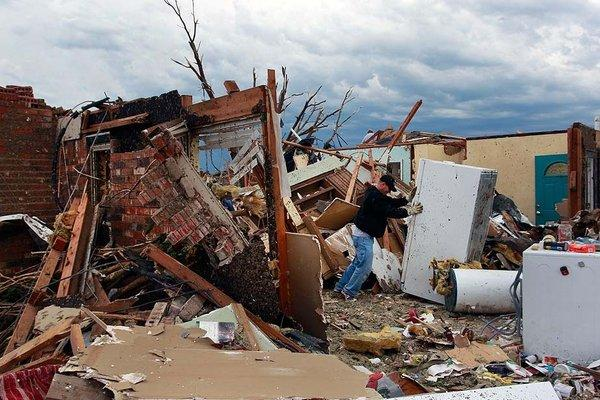 Rodney Heltcel salvages items from the wreckage of his home of 21 years that was destroyed Monday when a tornado moved through Moore, Okla.