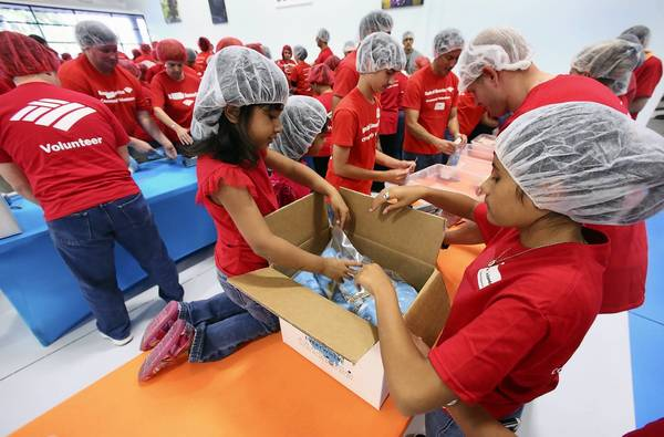 Aylah Shujaat, 5, (left, on the table), and Kiana Woodman, 14 (right), pack meals Tuesday, May 21, 2013, helping over 100 Bank of America volunteers including their family members assemble food packages at the Feeding Children Everywhere facility in Longwood. They are planning to package 15,000 meals that will be sent to Okalhoma to help feed victims.