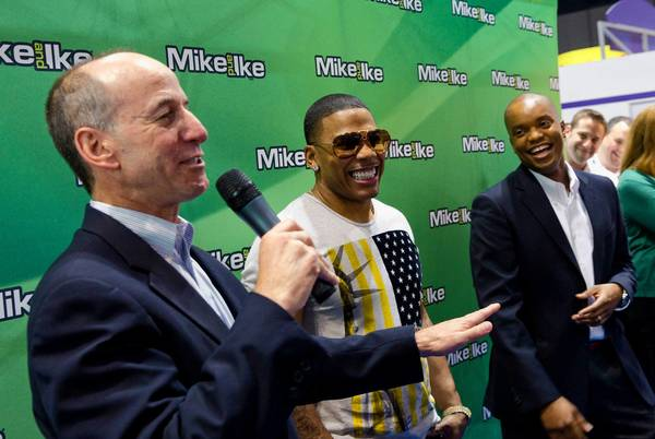 Rapper and actor Nelly, center, appears at the Mike and Ike candy booth at the Sweets & Snacks Expo at McCormick Place Convention Center on Tuesday. Nelly will promote the candy for the Just Born candy company. At left is David Yale, president and CEO of the company. At right is David Houston, a senior marketing manager for the company.