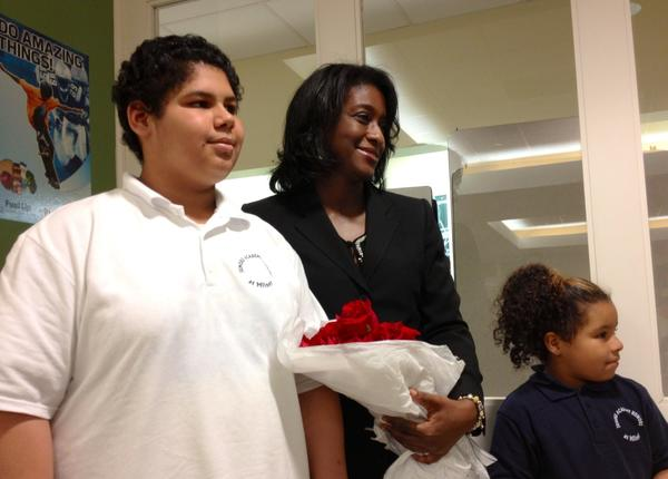Karen Lott, appointed the new principal of Jumoke Academy at Milner School Tuesday, poses for a picture with two students who gave her roses after the school board's approval. Lott starts the job in July.