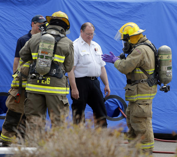 Mike Thompson, fire marshal with Aberdeen Fire and Rescue, center, watches as Tim Medenwald, right, puts on several pairs of rubber gloves as Medenwald and Joel Weig, back to camera left, were preparing to retrieve two envelopes from the U.S. Bank building at 320 South First Street Friday afternoon that were sent to the offices of U.S. Senators John Thune and Tim Johnson. They later recovered an envelope sent to U.S. Representative Kristi Noem. photo by john davis taken 5/17/2013