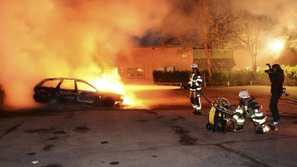 Firefighters extinguish a burning car, following riots in the Stockholm suburb of Kista late Tuesday night.