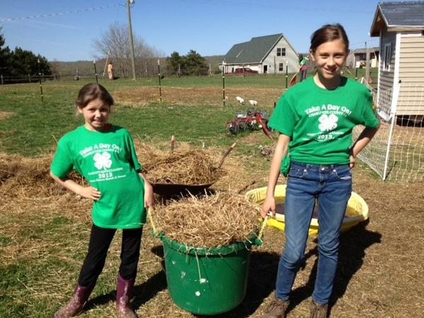 Josie Bollmann (left) and Maggee Behling pick up the barnyard at Second Chance Ranch in Boyne City.