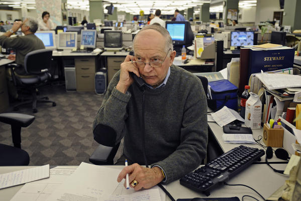Baltimore Sun crime reporter Richard Irwin is pictured in the Baltimore Sun newsroom calling area police departments.