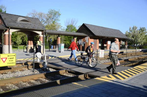 """A Glenview police officer ensures pedestrians cross the train tracks safely at Glenview Metra Station Thursday morning, May 16. Police were present this week to enforce ticketing for those who crossed in defiance of warning signals as part of """"Operation Lifesaver."""""""