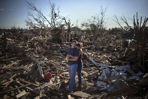 Danielle Stephan holds boyfriend Thomas Layton as they pause between salvaging through the remains of a family member's home one day after a tornado devastated the town Moore, Oklahoma, in the outskirts of Oklahoma City.
