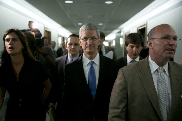 Tim Cook, chief executive officer of Apple, center, walks through a hallway during a break of the Senate Permanent Subcommittee on Investigations hearing in Washington.