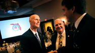 Gov. Rick Scott shakes the hands of Brandon Rodriguez, at right, and his dad Rocky Rodriguez, at center.Republican