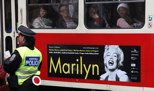 Passengers travel in a tram with an advertisement for a planned exhibition on Marilyn Monroe in central Prague.