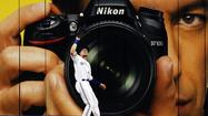 Blue Jays Rasmus makes a catch against the  Rays in front of a giant camera advertisemenduring their MLB baseball game in Toronto