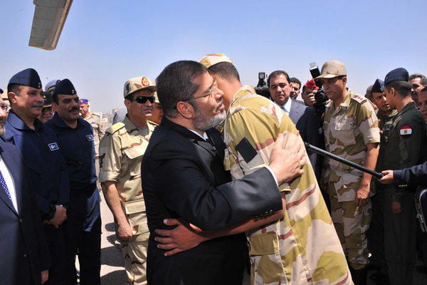 President Mohammed Morsi, center, in Cairo embraces a soldier who had been freed from captivity on Wednesday.