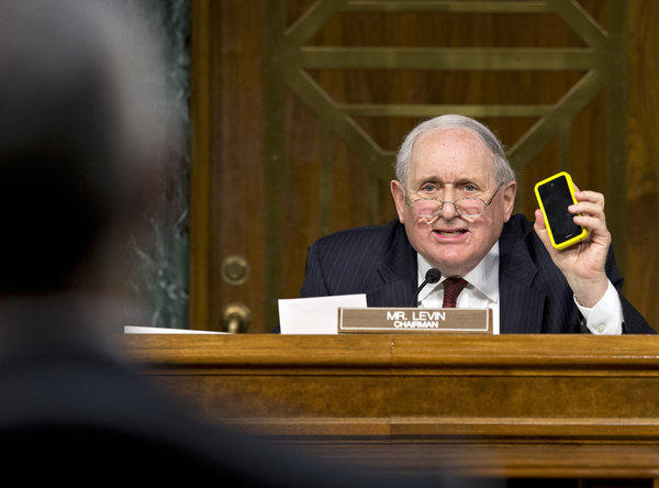 "Sen. Carl Levin (D-Mich.) holds up his iPhone as he tells Apple Chief Executive Tim Cook, ""We love the iPhone and the iPad."""