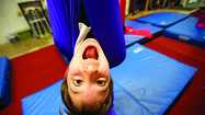 Julian Adam, 10, of Greenbelt, goofs around on the fabric trapeze before class.