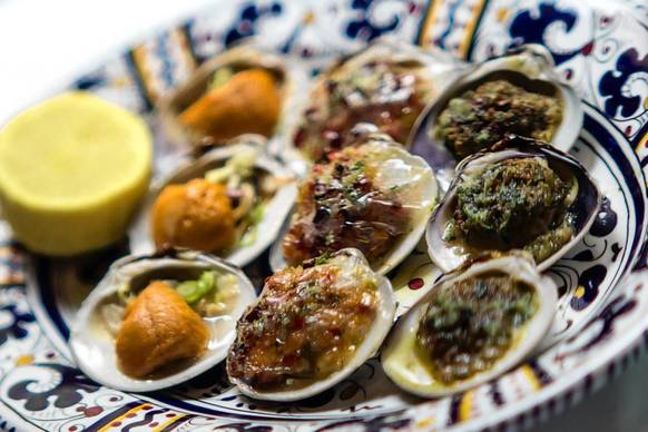 Assorted baked clams are served at Carbone. The clams are cooked in three ways: Oreganata with purposefully soggy breadcrumbs, Casino with bacon and peppers, and Fantasia with sweet sea urchin.