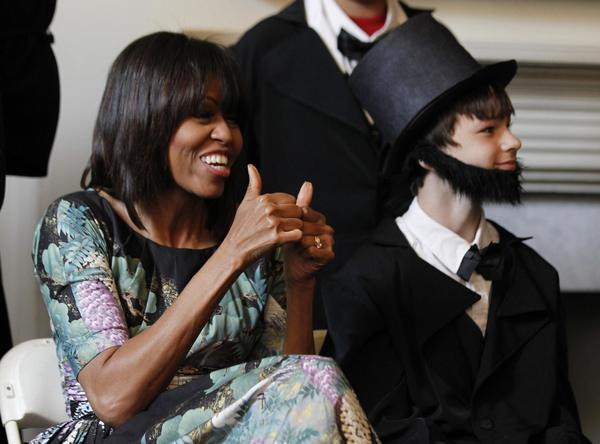 U.S. first lady Michelle Obama gestures alongside Aidan LeBlanc, a 12-year-old 6th grader dressed as Abraham Lincoln from Willow Springs Elementary School, in Fairfax, Virginia, as they participate in a play about the emancipation of slaves during Abraham Lincoln's presidency, at historic Decatur House in Washington, May 22, 2013.