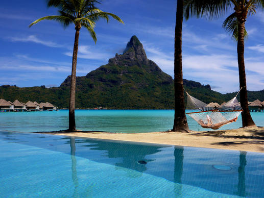 A guest reads a book on the beach at the InterContinental Bora Bora Resort and Thalasso Spa, commonly called the Thalasso, in Bora Bora. Mt. Otemanu looms in the background.