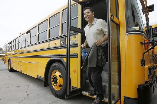 Fred Navarro, the superintendent of the Newport-Mesa Unified School District, steps off a school bus after spending the morning riding with kids on Wednesday.