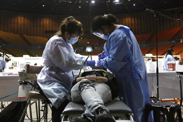 Dental hygienist Mary Kay Alexander, left, and dental assistant Erika Bravo work on a patient during the final day of the Remote Area Medical health fair and clinic at the Forum in Inglewood.