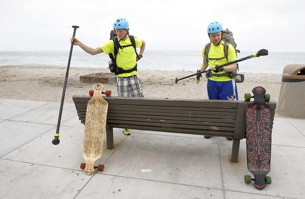 Cousins Kenton Durfee, left, and Mason Bennett gear up at Aliso Beach as they continue down the California coast on longboard skateboards to raise funds for Bridge of Love organization to benefit abandoned children in Romania.
